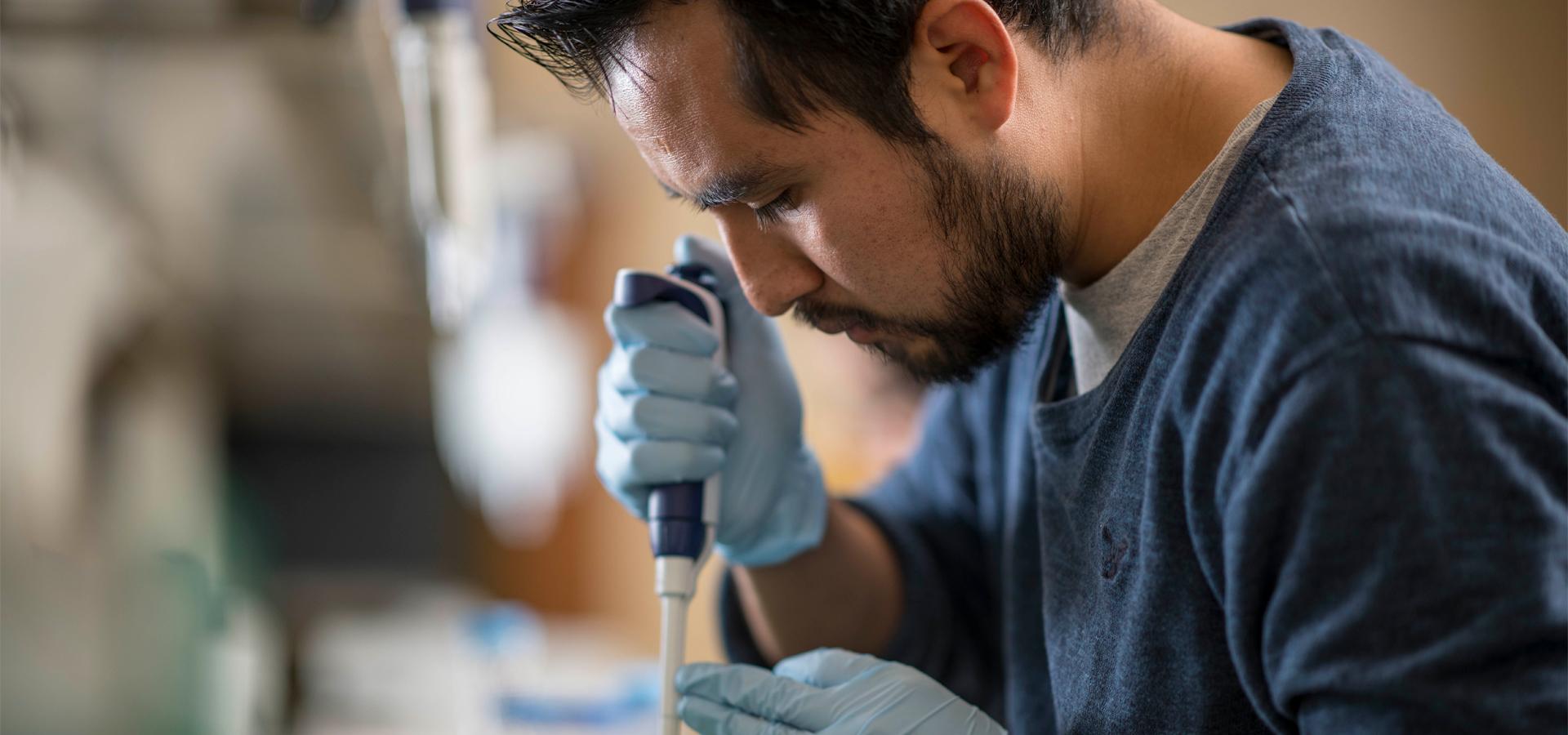 Researcher using a pipette